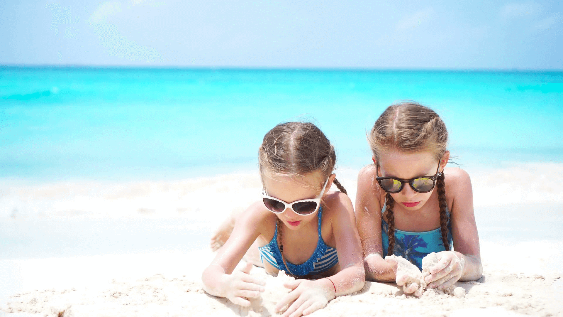 videoblocks-adorable-little-kids-play-with-sand-on-the-white-beach-two-girls-have-fun-on-summer-holidays_haxxsjqyjz_thumbnail-full01