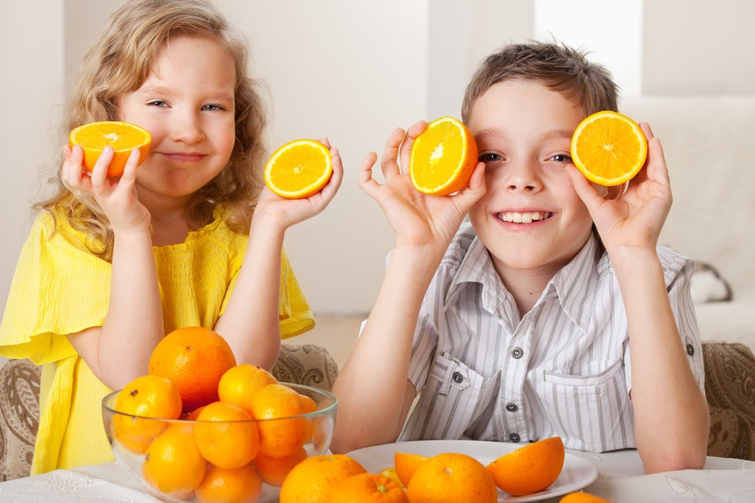 Children with oranges. Happy little girl and boy with fruit at home.