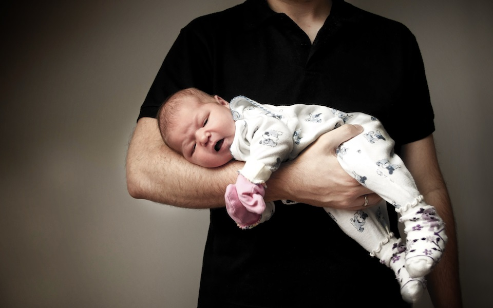 In father's arms - holding a newborn. Protection concept.